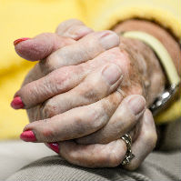 Elderly couple holds hands